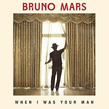 "Bruno Mars standing with his back turned opening a drapery, the words ""When I Was Your Man"" with capital font can be seen on the bottom of the picture, while the words ""Bruno Mars"" in red capital font are on the top of the image."
