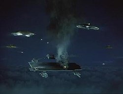 The scale model of an object that resembles an aircraft carrier hovering at high altitude emits fire and smoke. It is under missile attack from rotating, circular alien spacecraft surrounding it. The setting is night.