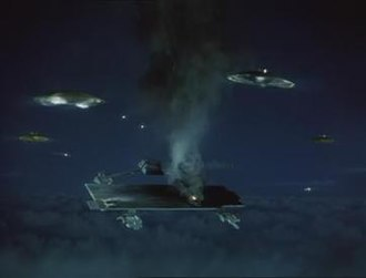 """Attack on Cloudbase - Mysteron spacecraft fire on Cloudbase. For reasons of economy, miniature models are present only in the foreground of the shot; the bright dots in the background are light bulbs added to the backdrop to give the impression of a larger attacking force. The design of the spacecraft was based on the reported appearance of alleged """"flying saucer"""" UFOs."""