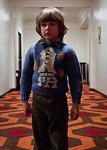 Danny Lloyd as the child character Danny Torrance in the 1980 film The Shining. He stands in a hotel hallway and wears a sweater with a rocketship on it.