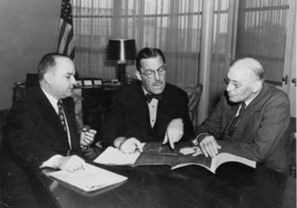 Grover Whalen - From left to right, José Gonzalez, Grover Whalen, and Dennis Nolan looking over plans for the Puerto Rico pavilion at the 1939 World's Fair.