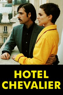 A young white couple stand on a hotel balcony looking out to the left of the frame. Only their upper bodies are shown. The man, who has shoulder-length hair and a trim moustache and who is wearing a grey suit, has his left arm around the short-haired woman, who is clad in a yellow hotel bathrobe and has her right hand on his shoulder.