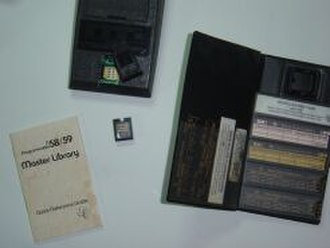 TI-59 / TI-58 - The Master Library Module shown removed from its socket in the back of the calculator. Magnetic card storage folio also shown.