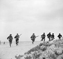 Men in extended line advance over a desert landscape