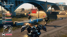 Screenshot of gameplay, showing the heads up display, and the Autobot Ironhide attacking Decepticons under a highway bridge.