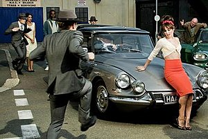 """Under the Sun (song) - Cheryl reclining on the bonnet of a classic car while a gang of gents in 50s suits dance around her in the music video for """"Under the Sun""""."""