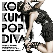 "A woman, dressed in a black dress with black-coloured accessories, leaning backwards, holding her hand against her mouth. The text ""Koda Kumi"", ""Pop Diva"", and ""You know I'm top diva, most beautiful, powerful, and talented girl on the planet... Are you ready for me?? Let's GO!!"" are imprinted on the left side of the cover."