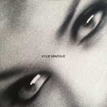 A black-and-white, and motion-blurred image of a woman's (Kylie Minogue) eyes. The song title and woman's name is superimposed on the image.