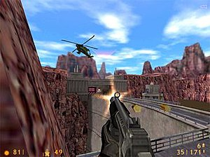 A video game screenshot depicting a gun being fired at a helicopter from a first-person perspective. The person from which the perspective of the image is taken is standing near a dam in a mountainous area, albeit with no visible water.