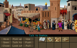 "A video game screenshot showing the two protagonists in the middle of a crowded marketplace. The lower part of the image shows a variety of objects on the right side and a number of verbs such as ""Pick up"", ""Use"" and ""Talk to"" on the left side. The mouse cursor is pointing at Sophia, making the current command ""Talk to Sophia""."
