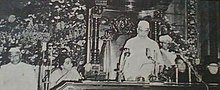 Photo of man in white cap/robe standing to speak at table