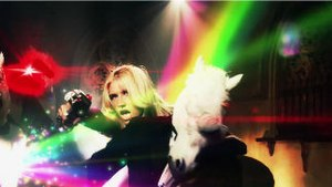 Blow (Kesha song) - A still from the music video showing Kesha as she shoots at Van der Beek while hiding behind a unicorn-headed party guest. Amongst the background, other unicorn-headed guests can be seen being killed from stray gun shots.