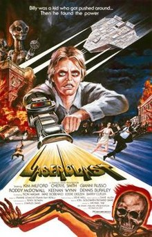 "A film poster with a young man with a laser gun extended from his arm, shooting out the title ""Laserblast"". A tagline at the top reads ""Billy was a kid who got pushed around... Then he found the power"". The top left shows two extraterrestrial aliens on top of a burning building, opposite an extraterrestrial spacecraft. Below the burning building, people are seen running away on the street. Credits for the film appear below the title, and a skeleton on fire is at the bottom of the image."