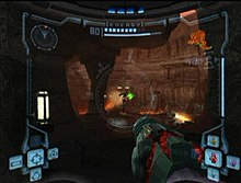 View of volcanic caverns; an enemy with a jetpack shoots a green ray at the player, whose weapon (a large cannon) is visible in the corner of the screen. The image is a simulation of the heads-up display of a combat suit's helmet, with a crosshair surrounding the enemy and two-dimensional icons relaying game information around the edge of the frame.