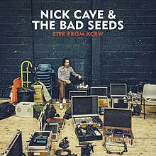 "A man sits on a chair against a black stone wall amid cases of musical equipment. Above, white block text reads ""Nick Cave & The Bad Seeds"" and red block text reads ""Live from KCRW""."