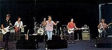 Cuatro machos sosteniendo guitarras, un quinto macho en el centro sostiene un pie de micrófono.