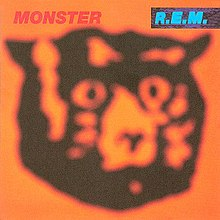 An album cover showing a blurred drawing of a cat's head in black against an orange background. The name of the album is in red text in the top-left corner of the cover and the band's name is in blue text on a black background in the top-right corner of the cover.