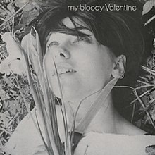 "A black and white image of a woman laying on grass. To the left side of her face, she holds a bunch of flowers and to the right side of her face, she holds a knife. The text on the top right corner of the image reads ""My Bloody Valentine""."