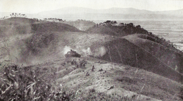 Infantry deployed on the crest of a hill, while in the background a tank provides support.