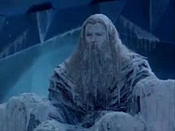 A man sits frozen in an icy throne room, he is covered in ice as icicles hang from his clothes and long beard.