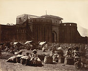 Shaniwar Wada: The palace of the Peshwas, founded by Peshwa Baji Rao I. The view looks towards the entrance gatehouse and outer walls of the palace, with a vegetable market on the open space in the foreground. Cira 1860