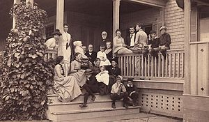 Deborah Fisher Wharton - A Newport family gathering in 1884. Deborah Fisher Wharton with her daughter Esther F.W. Smith and family on front porch steps of Esther and Ben Smith's summer house on Newport waterfront. Deborah is older woman sitting with white bonnet. Esther sits by post with Esther Hallowell on lap. Standing behind her is husband Benjamin R Smith. Anna Smith (Wood) leans against post. Next is William Wharton Smith, and sitting on rail, Anna Wharton (Morris), and far right, Edward Wanton Smith. Esther Morton Smith stands by left post. Behind Deborah are Robert and Hannah Haydock, parents of Sally Hallowell, with baby Susan on lap, sitting on step behind her 3 boys. Leaning on railing at left is Evelyn Meyer. Just below Deborah is Anna Hallowell and Polly Wharton against the post. Joanna Wharton (Lippincott) is sitting on upper step behind 2 boys.