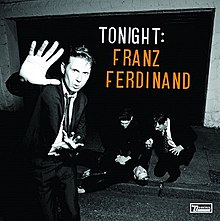 A black-and-white photograph of a man confronting a photographer while two others tend to a man who has fallen ill on the sidewalk The words Tonight in white and Franz Ferdinand in orange are displayed in the top-right of the photo