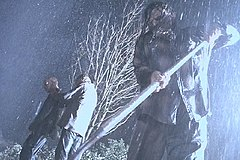 Three men in the rain, one is holding a shovel.