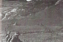 Two lines of evenly spaced soldiers wearing slouch hats advancing across a ridgeline