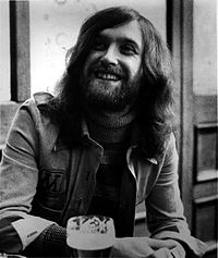 A young, bearded man, wearing a jacket over a striped turtleneck sweater, sits a table presumably in a bar or pub.