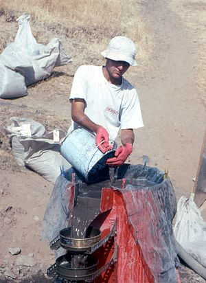 Paleoethnobotany - Flotation machine in use at Hallan Çemi, southeast Turkey, c. 1990. Note the two sieves catching charred seeds and charcoal, and the bags of archaeological matrix waiting for flotation. Photo: Mark Nesbitt
