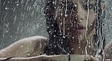 A portrait of a young brunette woman taking a shower.