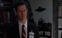 A man is dressed in a white shirt and black suit with a red and cream tie. An FBI badge is clipped on. Behind the man, there is a large poster featuring an UFO.