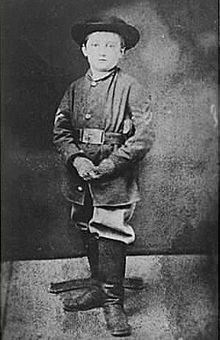 Boy wearing Union uniform, hat, and boots, looks into the camera.