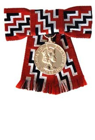 Queen's Service Medal - First version of the Queen's Service Medal on female ribbon