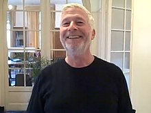 Head and shoulders of a man in his sixties with close-cropped white hair and a short beard, wearing a black T-shirt.