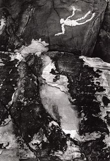 A black-and-white photograph of a Native American petroglyph.