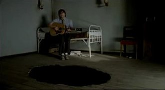 I Will Follow You into the Dark - In this screenshot of the main music video, Ben Gibbard plays his guitar in a sparse room while the ever-widening hole in the floor dominates the foreground.