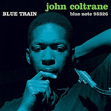 "Coltrane leans back with a reed in his mouth in a deep blue-on-black photo. The words ""BLUE TRAIN"" are written above his head in white followed by ""john coltrane"" in orange."