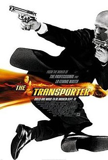 Jason Statham wearing a suit and holding two guns, in black and white.  A band of orange colour with the title Transporter is overlaid in the middle of the picture.