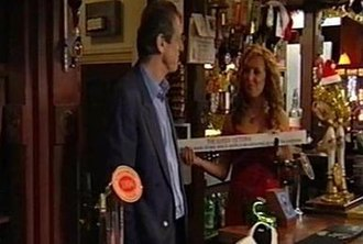 Watts family - Chrissie brandishes the Queen Vic licence now back in Watts hands, December 2004. After 15 years, Den was back behind the bar!