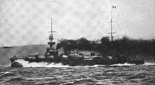 A large black ship, partially obscured by thick smoke from its funnels, creates a large bow wave as it plows through the water at high speed.