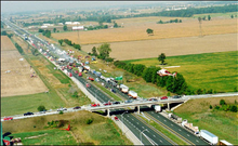 """A highway viewed from high above travels into the distance from the bottom-right to the top-left. An overpass allows a road to cross the highway near the bottom of the image. The surroundings are entirely agricultural. On the highway, several dozen vehicles are piled into each other. The middle of the large pileup is smoking."""