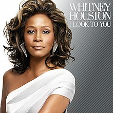 From left to right, the background fades from white to teal. In the foreground, slightly off-center stands an Afro-American woman in a white over-one shoulder dress. She is smiling and her long hair is flowing. In the right hand corner is her the name of the artist, Whitney Houston followed by the title of the album, I Look to You in a simple white font.