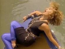 A blond woman with both her hands up in the air. The backdrop shows a number of houses with interconnecting channels. The woman wears a black top with a number of garlands around her neck, and a large chain-like belt. Her blond hair is curled and unkempt.