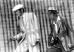 Black-and-white image of two men facing the left of frame, walking in front of a brick wall. A bold series of vertically striped shadows covers the entire image, the middle-aged man to the right wears a white fedora, a medium-dark suit, and an open-collared white shirt. In front of him, to the left of the image, a younger, taller man wears a cream-toned suit, a white beret and shirt, and a light striped tie, each man holds a pistol in his right hand.