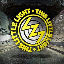 "Image shows the acronym ""LZ7"" in a yellow font in the style of a lightning bolt on top of three concentric grey circles. The grey circles are enclosed within a thin yellow circle, which is in turn enclosed within a circle of the words ""THIS LITTLE LIGHT·THIS LITTLE LIGHT·"" in a yellow font. This entire logo is set against a background of a black-and-white perspective view of an urban street at night, showing a road, walls and dark sky. The walls have graffiti on them."