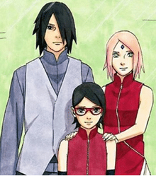 A colored manga image showing a girl with long, swept-back, dark hair wearing red-framed glasses and a sleeveless red tunic. Behind her to the viewer's left stands a young, tall man wearing a gray tunic and long-sleeved shirt; he has long, parted hair that covers his left eye. To his left, there is a shorter young woman with long pink hair and green eyes, wearing a sleeveless red tunic; her hands are placed on the girl's shoulders.