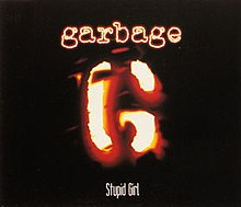 "A stylized ""G"" resembling a branding iron. Above is ""Garbage"" in neon-like letters, and below ""Stupid Girl""."