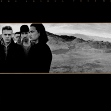 A landscape monochrome photograph of U2 in the desert sits in the center of a black background. U2 are standing on the left half of the photograph, with a mountain range on the right half. Tiny gold text reading
